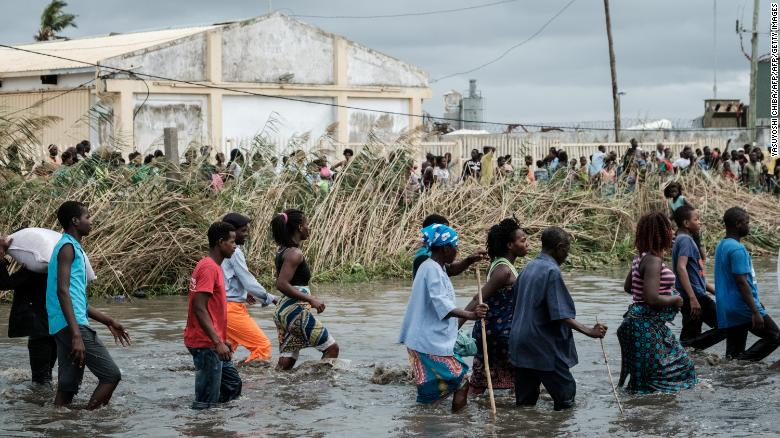 People carry Chinese rice from a warehouse surrounded by water after the Cyclone Idai hit the area, in Beira, Mozambique, on March 20, 2019.
