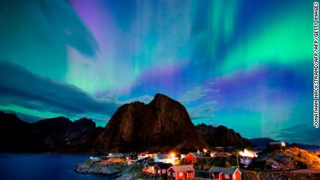 Cahaya utara menari di langit malam, tinggi di Lingkaran Arktik.