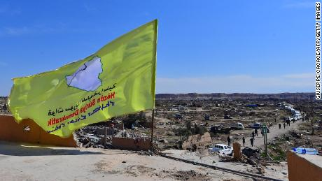 "A picture taken on March 23, 2019 shows the US-backed Syrian Democratic Forces' (SDF) flag atop a building in the Islamic State group's last bastion in the eastern Syrian village of Baghuz after defeating the jihadist group. - The Kurdish-led forces pronounced the death of the Islamic State group's nearly five-year-old ""caliphate"" on March 23, 2019 after flushing out diehard jihadists from their very last bastion in eastern Syria. (Photo by GIUSEPPE CACACE / AFP)        (Photo credit should read GIUSEPPE CACACE/AFP/Getty Images)"