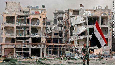 TOPSHOT - A member of the Syrian pro-government forces carries the national flag as he stands in front of damaged buildings in the Yarmuk Palestinian refugee campon the southern outskirts of the capital Damascus on May 22, 2018. - The government seized earlier in the week the Yarmuk Palestinian camp and adjacent neighbourhoods of Tadamun and Hajar al-Aswad from the Islamic State (IS) group , putting Damascus fully under its control for the first time since 2012. (Photo by LOUAI BESHARA / AFP) / The erroneous mention[s] appearing in the metadata of this photo by LOUAI BESHARA has been modified in AFP systems in the following manner: [Yarmouk Palestinian refugee camp ] instead of [Hajar al-Aswad neighbourhood]. Please immediately remove the erroneous mention[s] from all your online services and delete it (them) from your servers. If you have been authorized by AFP to distribute it (them) to third parties, please ensure that the same actions are carried out by them. Failure to promptly comply with these instructions will entail liability on your part for any continued or post notification usage. Therefore we thank you very much for all your attention and prompt action. We are sorry for the inconvenience this notification may cause and remain at your disposal for any further information you may require.        (Photo credit should read LOUAI BESHARA/AFP/Getty Images)