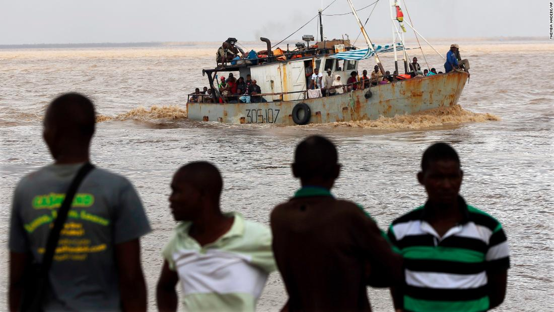 Men watch the arrival of a boat carrying displaced families rescued from a flooded area of Mozambique's Buzi district on March 23.