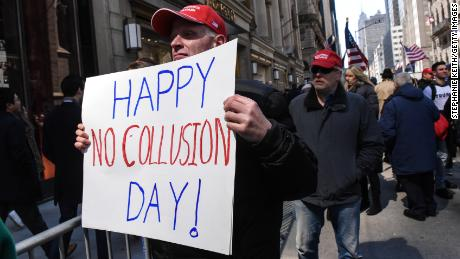 "A man holds a sign that reads ""Happy No Collusion Day"" while people attend a rally in support of President Donald Trump near Trump Tower on March 23, 2019 in New York City."