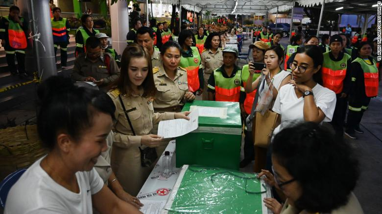 People watch the vote counting process at a polling station in Bangkok on March 24, 2019 after polls closed in Thailand's general election.