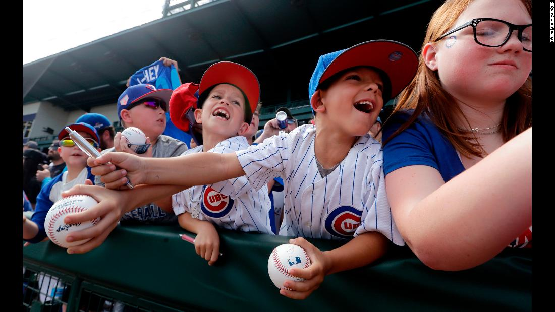 Reed Tomey, 6, center right, pushes away the arm of his brother, Rhett, 8, as the two attempt to get autographs from Chicago Cubs players before a spring training game against the Seattle Mariners in Mesa, Arizona, on Tuesday, March 19.