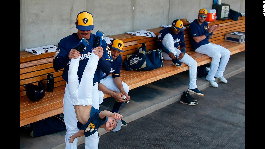 Brewers infielder Tyler Saladino plays in the dugout with Christopher Perez, son of his teammate Hernán Pérez, before a spring training baseball game against the Texas Rangers on Tuesday, March 19 in Phoenix, Arizona.