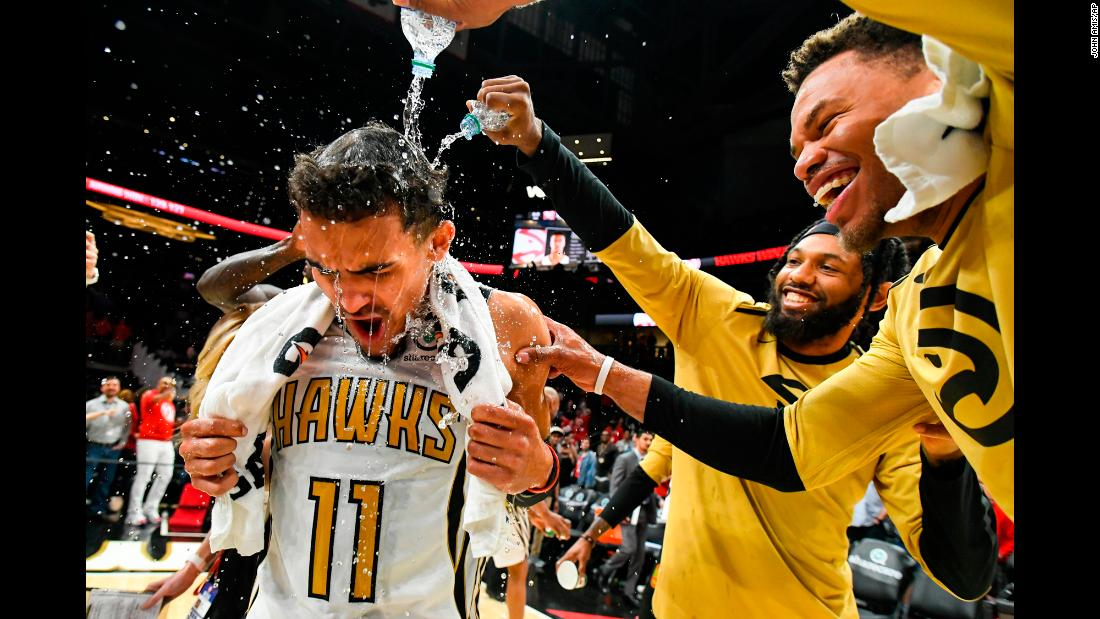 Atlanta Hawks guard Trae Young is doused with water by teammates DeAndre' Bembry and Justin Anderson, right, after making a game-winning basket in the final moments of an NBA game against the Philadelphia 76ers on Saturday, March 23 in Atlanta.