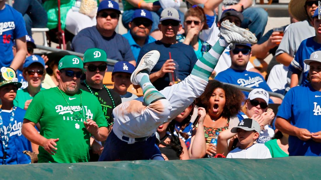Los Angeles Dodgers third baseman Justin Turner falls into the stands while chasing a foul ball during the third inning of a spring training baseball game against the Milwaukee Brewers in Glendale, Arizona on Sunday, March 17.