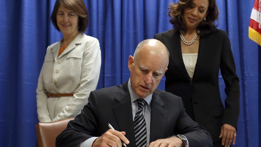 Harris watches California Gov. Jerry Brown sign copies of the California Homeowner Bill of Rights in July 2012.