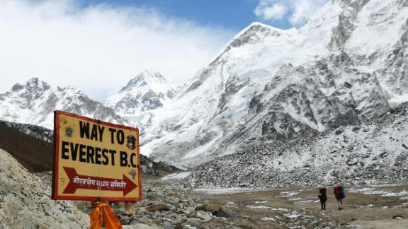 In this photograph taken on April 26, 2018, a sign points towards the Everest base camp while two  trekkers walk in the Everest region in Solukhumbu district some 140km northeast of Nepal