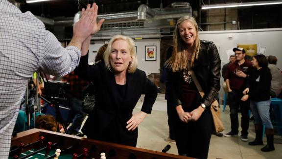 Gillibrand high-fives a foosball opponent while campaigning in Manchester, New Hampshire, in March 2019.