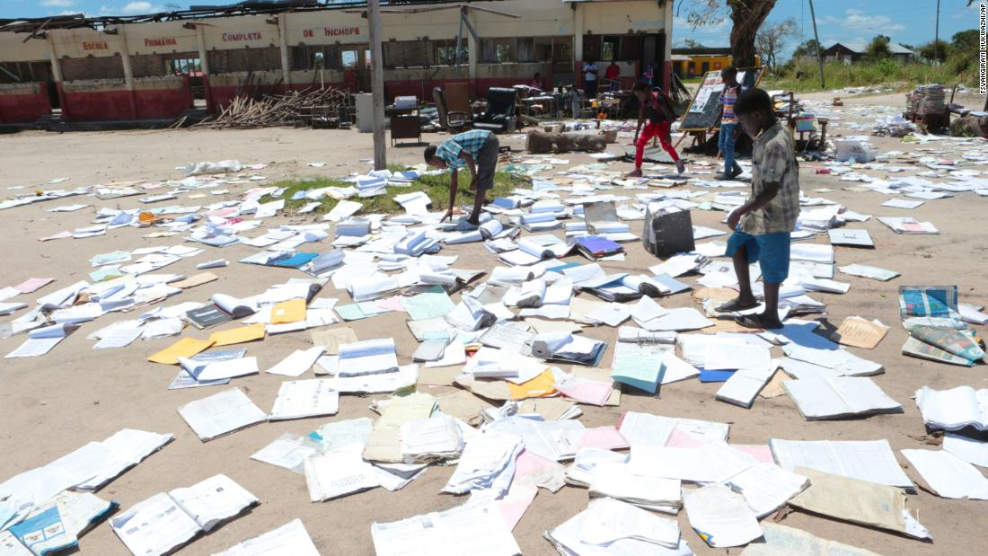 Children pick up books left to dry after Cyclone Idai damaged their school in Inchope, Mozambique, on March 25.