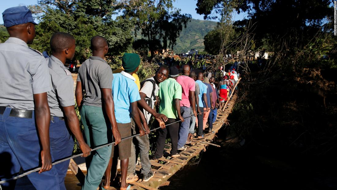 Survivors of the cyclone cross a temporary foot bridge to receive aid in Chipinge, Zimbabwe, on March 25.