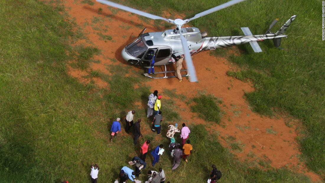 People unload relief supplies from a helicopter in Chimanimani, Zimbabwe, on March 24.