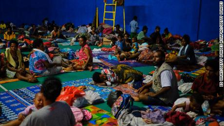 Indonesians displaced by the floods sleep on a badminton court at a local government building in Sentani.