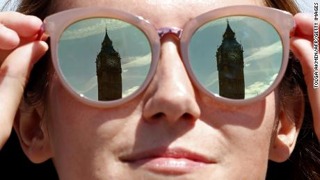 A tourist has the Elizabeth Tower, commonly referred to as Big Ben reflected in her mirror lenses as the sun shines in central London on June 16, 2017.