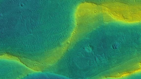 A photo of a preserved river channel on Mars, taken by an orbiting satellite, with color overlaid to show different elevations. Blue is low and yellow is high.