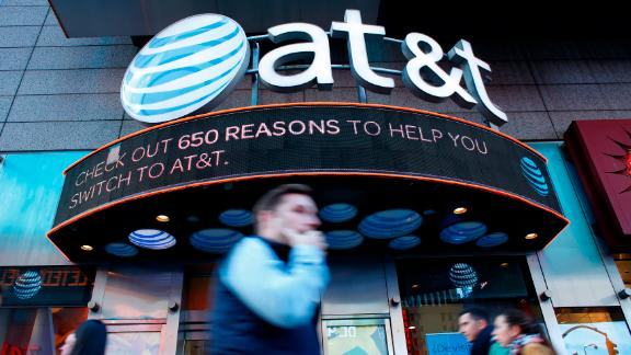 People walk past an AT&T store in New York on October 23, 2016.  AT&T unveiled a mega-deal for Time Warner that would transform the telecom giant into a media-entertainment powerhouse positioned for a sector facing major technology changes. The stock-and-cash deal is valued at $108.7 billion including debt, and gives a value of $84.5 billion to Time Warner -- a major name in the sector that includes the Warner Bros. studios in Hollywood and an array of TV assets such as HBO and CNN. / AFP / KENA BETANCUR        (Photo credit should read KENA BETANCUR/AFP/Getty Images)