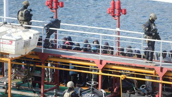 Maltese army forces and migrants pictured on board the hijacked tanker in Valletta.