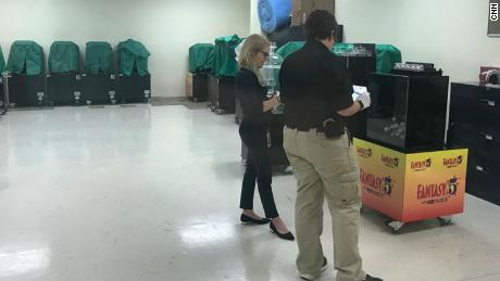 Lottery security agents check a Florida state lottery machine.