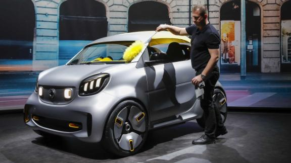 A worker cleans a Smart Forease electric concept at the Geneva Auto Show in March.