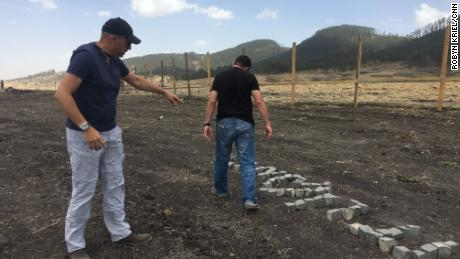 Moshe Biton and Ilan Matsliah place stones spelling out their dead brothers names in Hebrew at the site.