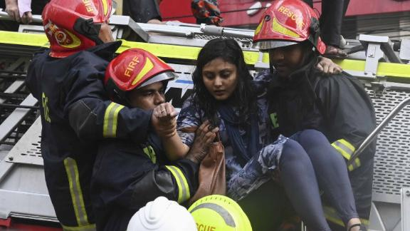 Bangladeshi firefighters rescue a woman from a burning office building in Dhaka on March 28, 2019. - A huge fire tore through a Dhaka office block March 28 killing at least five people with many others feared trapped in the latest major inferno to hit the Bangladesh capital. (Photo by MUNIR UZ ZAMAN / AFP)        (Photo credit should read MUNIR UZ ZAMAN/AFP/Getty Images)