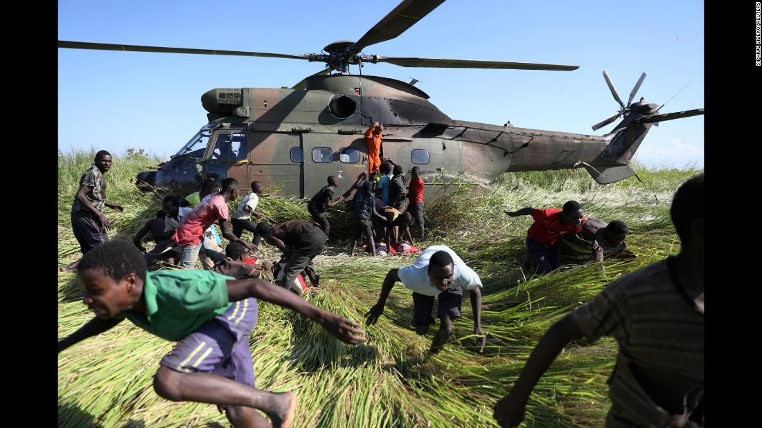"People in Nhamatanda, Mozambique, duck their heads after collecting food supplies from a South African military helicopter on Tuesday, March 26. Cyclone Idai <a href=""https://www.cnn.com/2019/03/24/africa/mozambique-cyclone-idai-destruction/index.html"" target=""_blank"">ripped through Mozambique</a> earlier this month, killing hundreds of people."