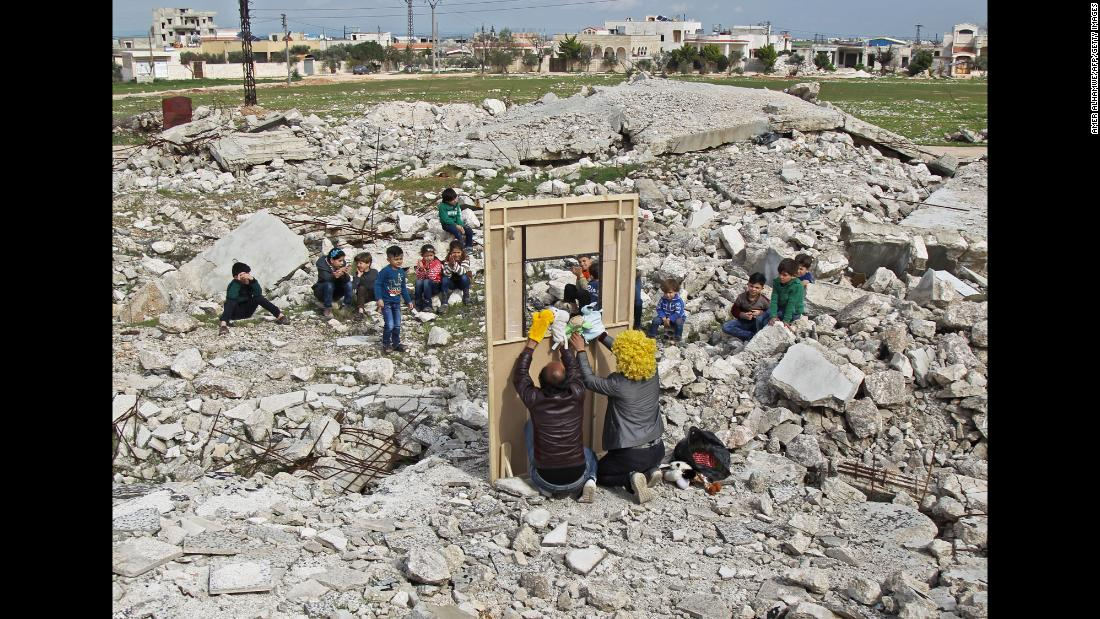 Syrian actors entertain children through a makeshift puppet theater that was set up in the war-torn city of Saraqib on Wednesday, March 27.