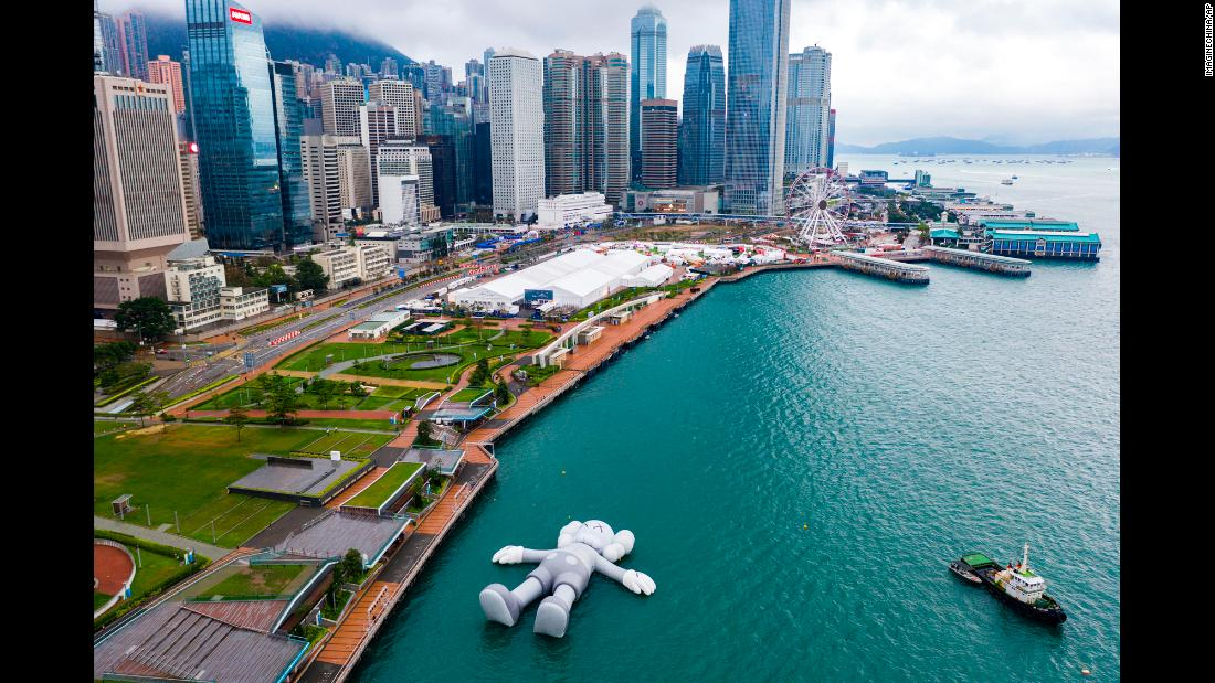 "An inflatable sculpture by the American artist KAWS is docked at Hong Kong's Victoria Harbour on Sunday, March 24. <a href=""https://www.cnn.com/style/article/kaws-holiday-hong-kong-art/index.html"" target=""_blank"">The floating sculpture</a> is 37 meters long (121 feet)."