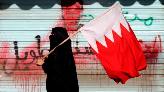 A Bahraini anti-government protester carries the national flag past anti-government graffiti sprayed over by authorities in 2013.