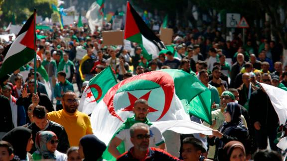 Demonstrators march with national flags during a protest in Algiers, Algeria, March 29, 2019. Algerians taking to the streets for their sixth straight Friday of protests aren't just angry at their ailing president, they want to bring down the entire political system that has sustained him. (AP Photo/Toufik Doudou)
