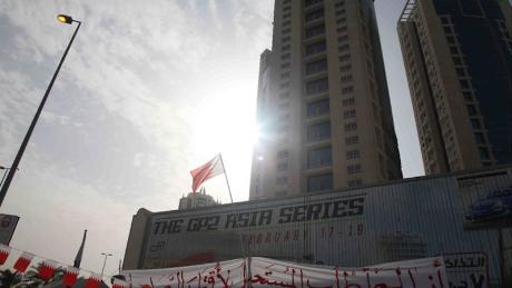 A protest sign is draped over a motorsport advertisement at the now-demolished Pearl Monument in Manama, during the 2011 Arab Spring protests.