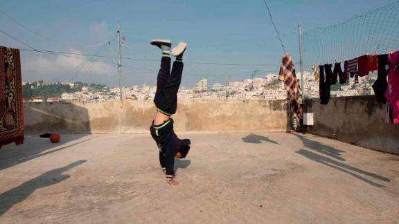 Zein Idris plays on the rooftop of his house in Hebron.