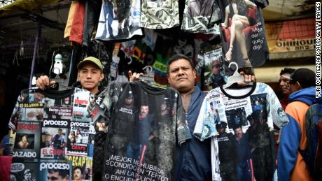 "Street vendors show T-shirts with pictures of Mexican drug lord Joaquin ""El Chapo"" Guzman Loera and Mexican actress Kate del Castillo (top, R) at Tepito neighborhood, in Mexico City on January 29, 2015. ""El Chapo"" is a registered brand of jewelry, photography equipment, toys and hats in Mexico. According to public registries of the Mexican Institute of Intellectual Property (IMPI), in the last years there are some 10 registries of ""El Chapo"" trademark, four of them requested by Alejandrina Gisselle Guzman Salazar, who is supposed to be Guzman Loera's daughter.  AFP PHOTO/ Yuri CORTEZ / AFP / YURI CORTEZ        (Photo credit should read YURI CORTEZ/AFP/Getty Images)"