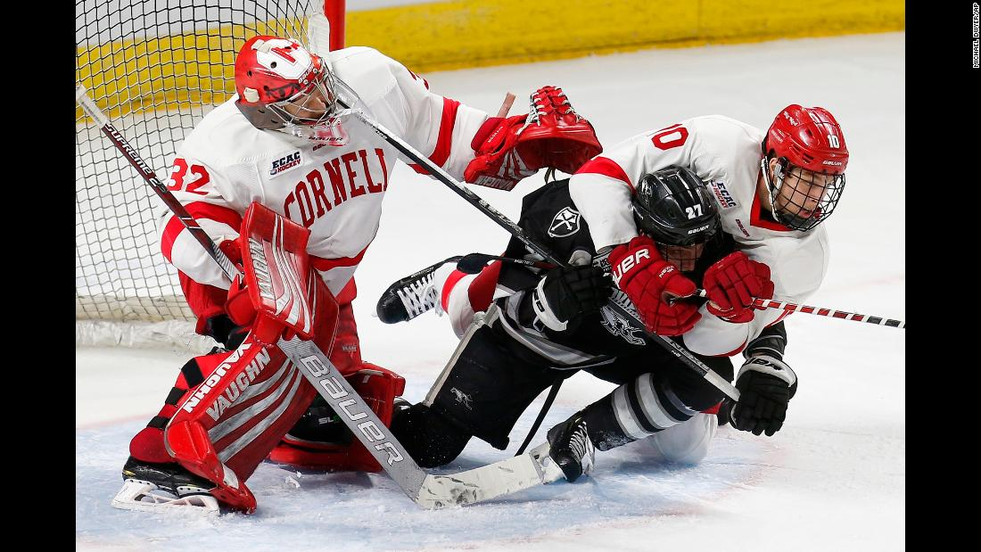 Providence's Tyce Thompson (27) falls to the ice with Cornell's Brendan Smith (27) in front of Cornell goalie Austin McGrath (32) during the second period of the NCAA Division I East Regional final men's hockey game in Providence, Rhode Island, on Sunday, March 31.
