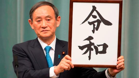 """Japan's Chief Cabinet Secretary Yoshihide Suga announces the new era name, """"Reiwa,"""" during a press conference in Tokyo."""