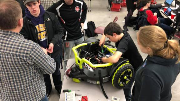 Farmington High School freshman Alex Treakle, working on the car, said he was glad he could help.