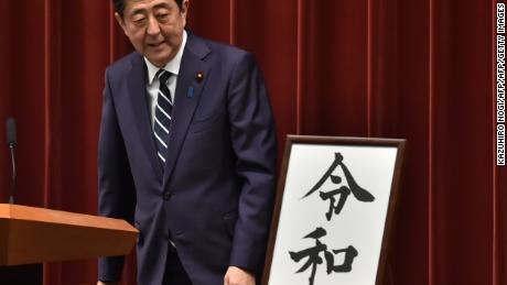 Japan's Prime Minister Shinzo Abe looks at a calligraphy rendering of the new era's name as he leaves a press conference.