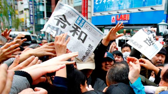 People reach for a copy of extra edition of the Sankei Shimbun newspaper reporting the name of new era.