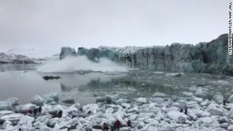 Tourists scramble to avoid a wave caused by a glacier collapse