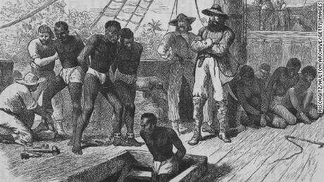 circa 1835:  Slaves aboard a slave ship being shackled  before being put in the hold.  Illustration by Swain  (Photo by Rischgitz/Getty Images)