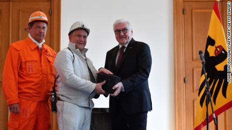 A firefighter and a miner hand over a symbolic last piece of black coal extracted in Germany to President Frank-Walter Steinmeier (R) on April 3, 2019, in Berlin.