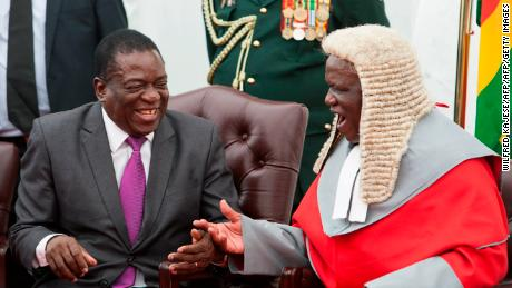 Zimbabwe's President Emmerson Mnangagwa, left, shakes hands with the country's chief justice Luke Malaba.
