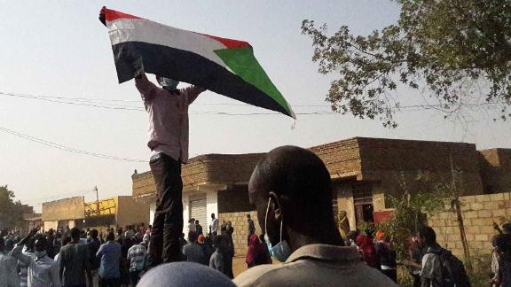 """A Sudanese protester waves a national flag during an anti-government demonstration in the capital Khartoum's twin city of Omdurman on January 31, 2019. - Sudanese police fired tear gas at crowds of demonstrators in the capital and other cities today, witnesses said, as fresh protests demanded an end to President Omar al-Bashir's three-decade rule.Chanting """"freedom, peace, justice"""", the rallying cry of the protest movement that has rocked Sudan for weeks, demonstrators took to the streets in both Khartoum and Omdurman. (Photo by STRINGER / AFP)        (Photo credit should read STRINGER/AFP/Getty Images)"""