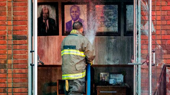 A firefighter stands outside the door to Mt. Pleasant Baptist Church on Thursday.