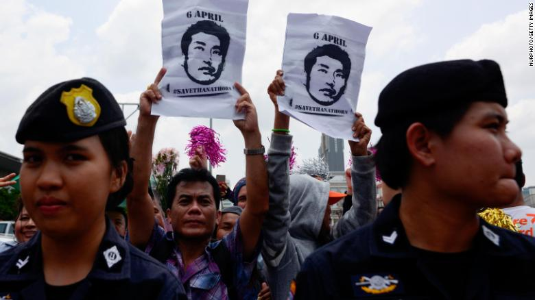Thanathorn's supporters hold posters bearing his likeness with the hashtag #SaveThanathorn.