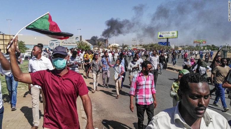 Sudanese protesters waive the national flag as they march toward the army headquarters.