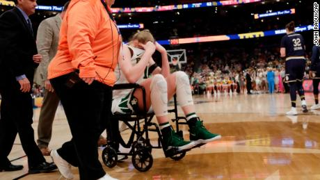 Baylor forward Lauren Cox is assisted off the court after she went down with injury.