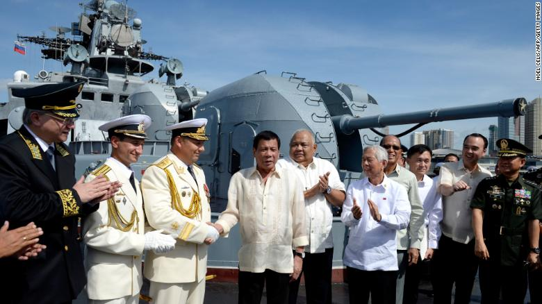Philippines' President Rodrigo Duterte (4th L) shake hands with Russia's Rear Admiral Eduard Mikhailov (3rd L) onboard the Russian anti-submarine navy ship Admiral Tributs in Manila on January 6, 2017.