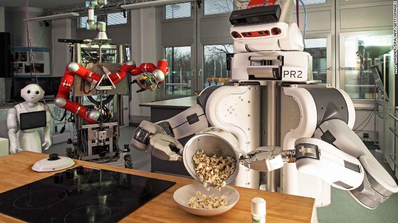 2017年3月8日,机器人在德国西北部不来梅大学人工智能研究所(AI)将爆米花从烹饪锅中倒入碗中。